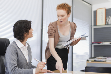 consulted: Businesswomen talking in office