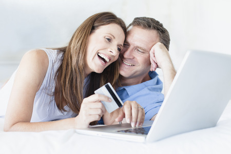 arrears: Couple shopping online on bed