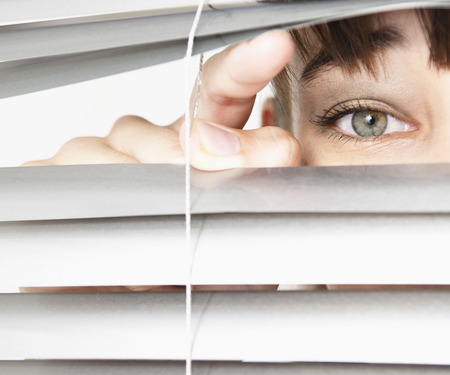 detects: Woman peeking through blinds LANG_EVOIMAGES