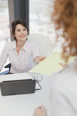 Businesswoman turning in folder to boss