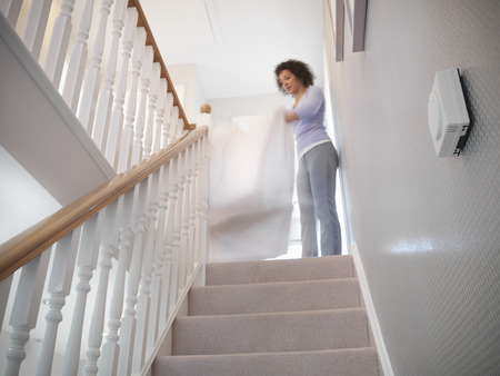 vibrations: Woman shaking out sheets on staircase LANG_EVOIMAGES