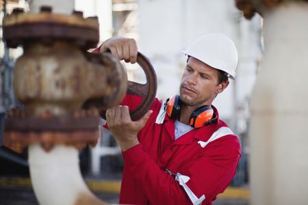 Worker adjusting gauge at chemical plant LANG_EVOIMAGES