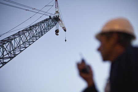 Crane over worker at oil refinery LANG_EVOIMAGES