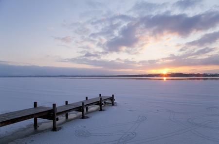 Pier jutting out into frozen lake