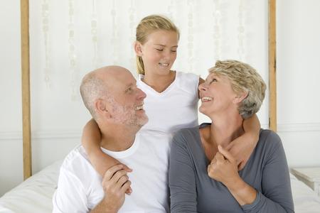 grampa: Older couple hugging granddaughter