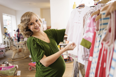 Pregnant woman buying baby clothes LANG_EVOIMAGES