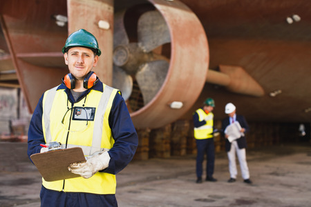 consulted: Worker carrying clipboard on dry dock LANG_EVOIMAGES