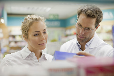 resolving: Pharmacist helping patient in store LANG_EVOIMAGES