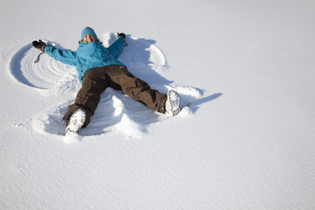 mischeif: Woman making snow angel on field