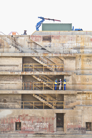 consulted: Workers talking on steps on dry dock