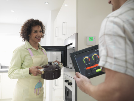 women's issues: Man using tablet computer in kitchen