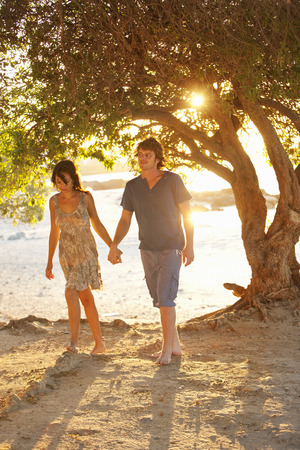 Couple walking barefoot in park LANG_EVOIMAGES