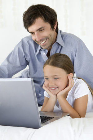 Father and daughter using laptop LANG_EVOIMAGES