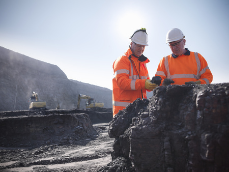 Workers inspecting coal at mine LANG_EVOIMAGES