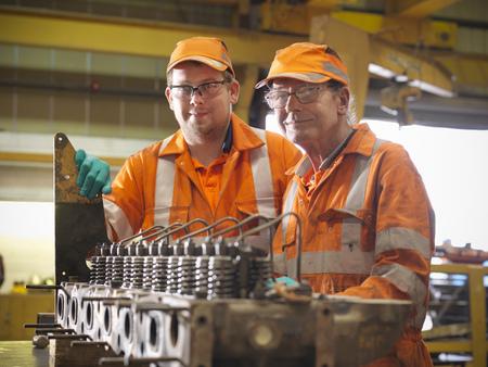 the elderly tutor: Engineer teaching apprentice in factory