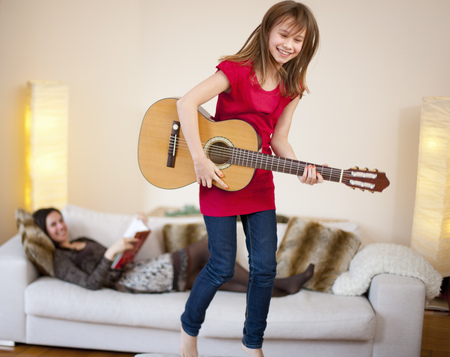 tomes: Girl playing guitar in living room LANG_EVOIMAGES