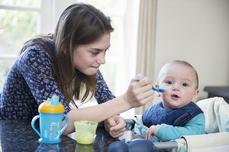 sitter: Girl feeding baby brother at table