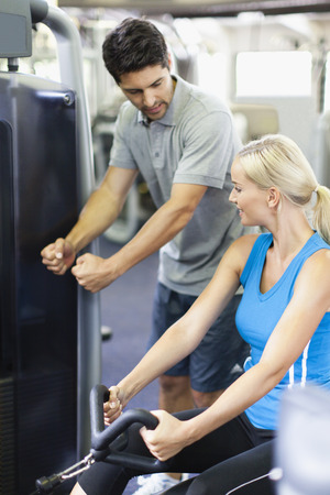 taught man: Woman working with trainer in gym