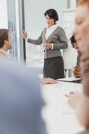 strategize: Businesswoman talking in meeting LANG_EVOIMAGES