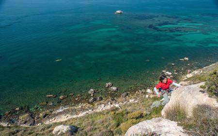 Woman climbing rocky coastal cliff