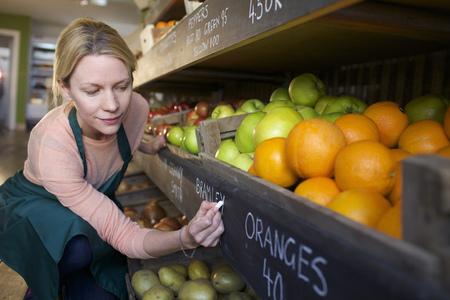 agachado: Grocer labeling produce para la venta LANG_EVOIMAGES