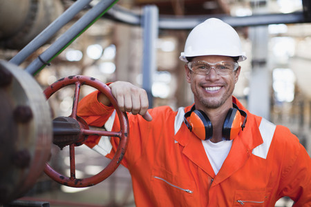 coordinating: Worker smiling at oil refinery