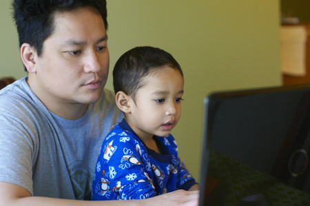 taught man: Father and son using computer together