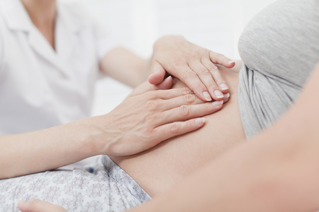 caregivers: Doctor examining pregnant womans belly