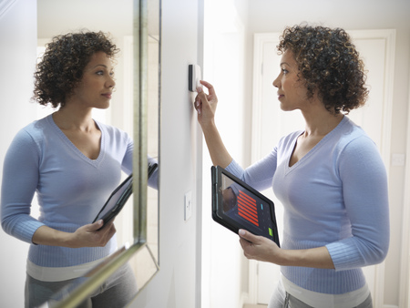 profile measurement: Woman adjusting thermostat in home LANG_EVOIMAGES