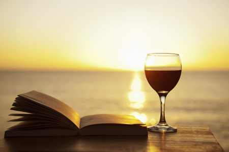 Glass of wine and book on table outdoors LANG_EVOIMAGES