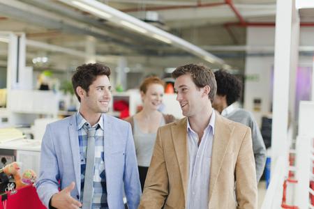 motioning: Businessmen walking together in office LANG_EVOIMAGES