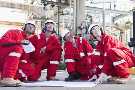 coordinating: Workers with blueprints at oil refinery