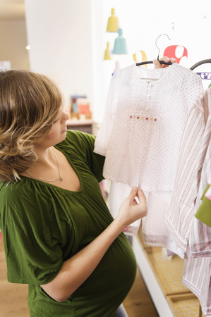 browses: Pregnant woman buying baby clothes LANG_EVOIMAGES