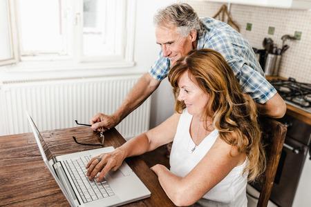 the elderly tutor: Older couple using laptop in kitchen LANG_EVOIMAGES