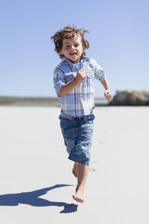 Boy running on sandy beach LANG_EVOIMAGES