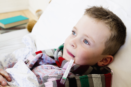 sickly: Boy with thermometer in mouth in bed