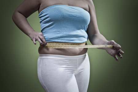 check out: Woman measuring her waistline LANG_EVOIMAGES