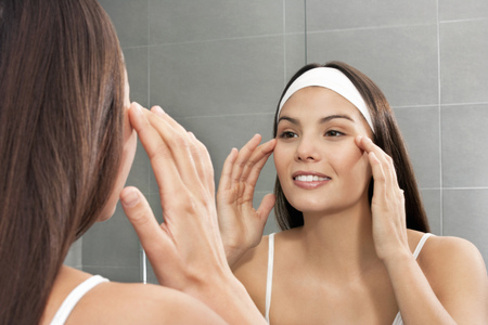 matured: Woman examining her face in mirror