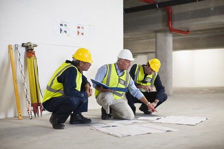 strategize: Workers reading blueprints on site