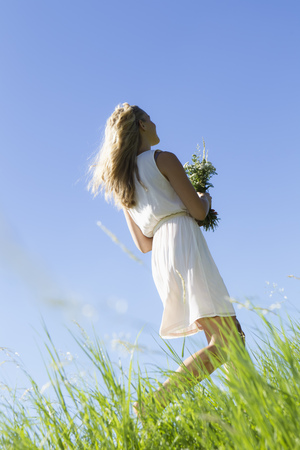 Woman carrying bouquet in tall grass