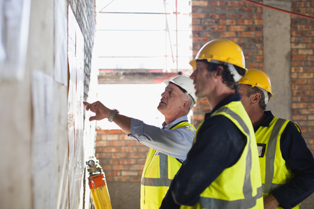 resolving: Workers reading blueprints on site