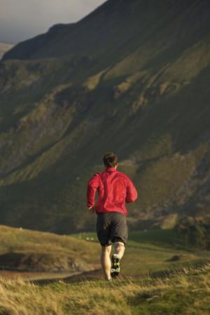 mountainous: Man running on rural mountain road LANG_EVOIMAGES