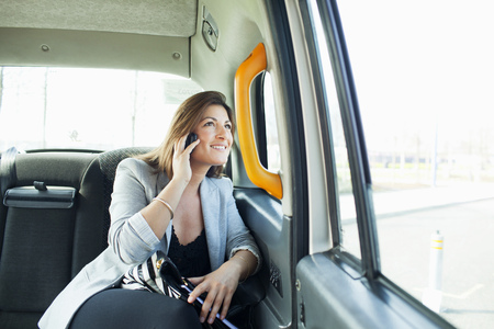 commuting: Businesswoman on cell phone in taxi