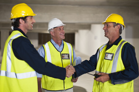 consent: Workers shaking hands on site