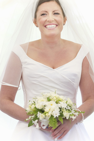 marrying: Smiling bride holding bouquet LANG_EVOIMAGES