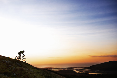 north western european descent: Mountain biker riding down hillside