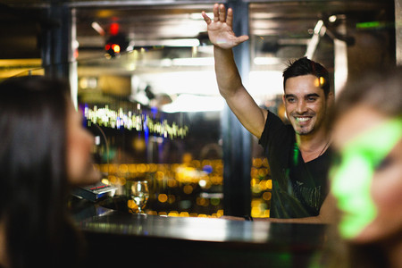Bartender waving to customers in bar