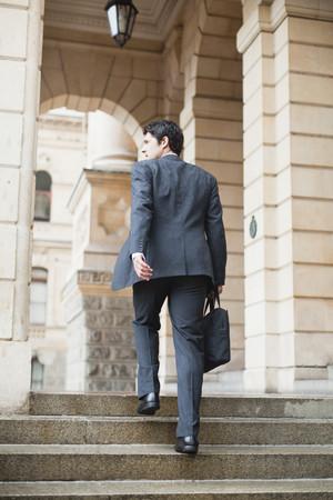 ascends: Businessman climbing steps of building