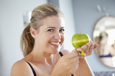 levantar peso: Sonriente mujer medir la manzana