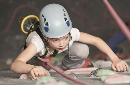 Girl climbing indoor rock wall